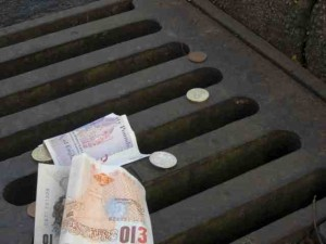 Money falling down a drain