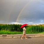 Woman walking under an umbrella with a rainbow